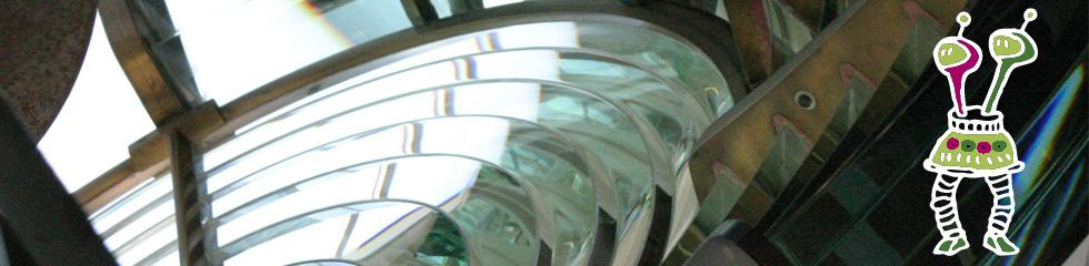 Two robots looking at a lighthouse lens.